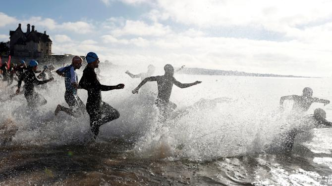 Participants run into the Atlantic Ocean as they begin the swimming section of a triathlon in Cascais