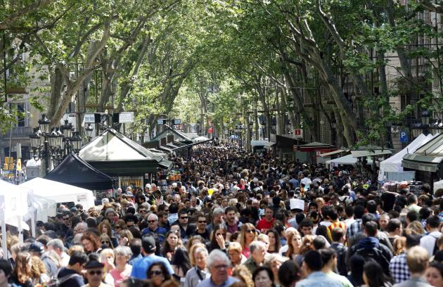 People walk along Las Ramblas street during traditional Sant Jordi's day celebrations in Barcelona