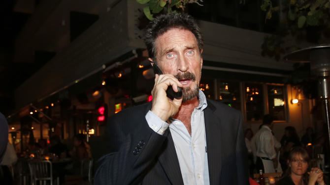 Anti-virus software founder John McAfee talks on his mobile phone as he walks on Ocean Drive in the South Beach area of Miami Beach, Fla., on his way to dinner Wednesday, Dec 12, 2012. McAfee arrived in the U.S. on Wednesday night after being deported from Guatemala, where he had sought refuge to evade police questioning in the killing of a man in neighboring Belize. (AP Photo/Alan Diaz)