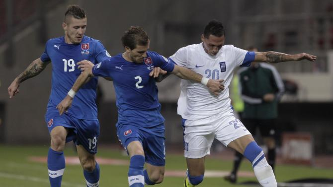 Greece's Cholebas is challenged by Slovakia's Pekarik and Kucka during the 2014 World Cup qualifying soccer match at Karaiskaki stadium in Piraeus near Athens