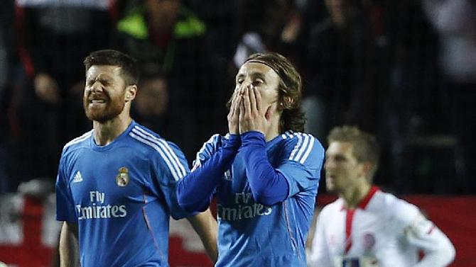 Real Madrid's Luka Modric from Croatia, right, and Xavi Alonso, left, react against Sevilla during their La Liga soccer match at the Ramon Sanchez Pizjuan stadium, in Seville, Spain, Wednesday, March 26, 2014