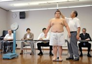 A young sumo wrestler is examined during a physical checkup in July for entry into professional sumo wrestling in Nagoya in Aichi prefecture. Sumo officials hope to attract new recruits from players rejected by baseball clubs