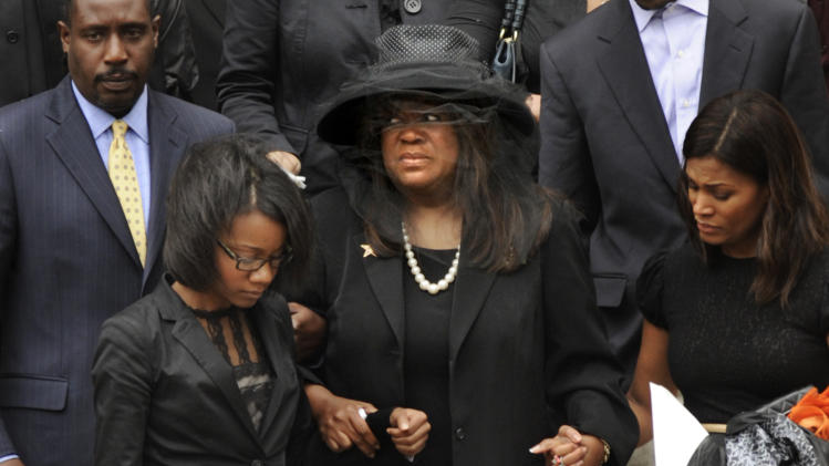Chaz Ebert, center, wife of film critic Roger Ebert leaves Holy Name Cathedral after his funeral in Chicago, April 8, 2013. The Pulitzer Prize-winning movie reviewer died Thursday, April 4 at age 70 after a long battle with cancer. (AP Photo/Paul Beaty)