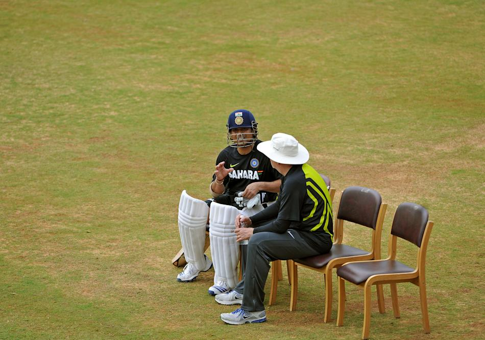 Indian cricketer Sachin Tendulkar (L) gestures during a conversation with the team's coach Duncan Fletcher during the team's practice session at the M. Chinnaswamy Stadium in Bangalore on August 29, 2