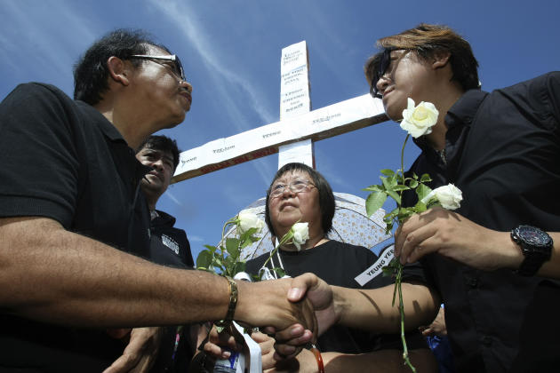 Dante Jimenez, left, head of a private watchdog Volunteers Against Crime and Corruption, gives white roses as he conveys his sympathies to Tse Chi Kin, right, brother of the late Masa Tse, a Hong Kong