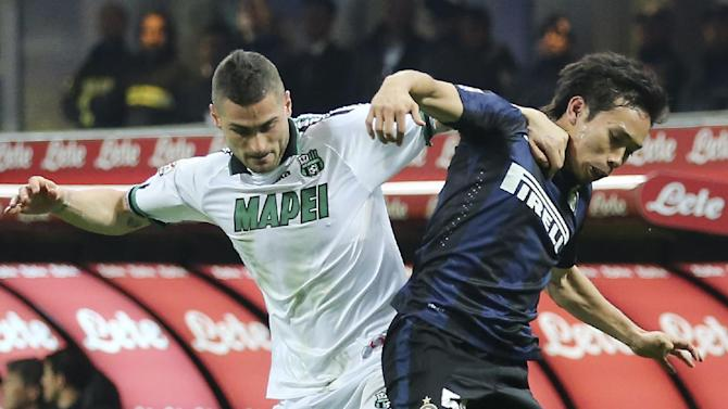 Inter Milan defender Yuto Nagatomo, right, of Japan, challenges for the ball with Sassuolo defender Aleandro Rosi during the Serie A soccer match between Inter Milan and Sassuolo at the San Siro stadium in Milan, Italy, Sunday, Feb. 9, 2014