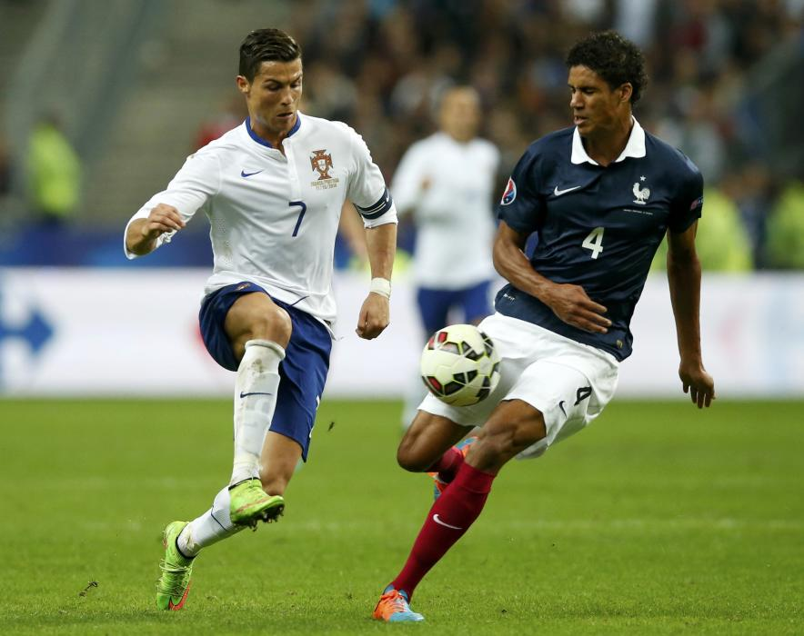 Portugal's Ronaldo challenges France's Varane during their friendly soccer match at the Stade de France in Saint-Denis