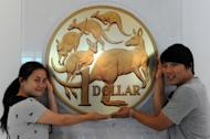 Chinese tourists pose for a photo next to a giant Australian dollar display at the Royal Australian Mint in Canberra. Chinese and Japanese tourists are increasingly flocking to Australia, boosting the overall March quarter visitor numbers Down Under, according to the government
