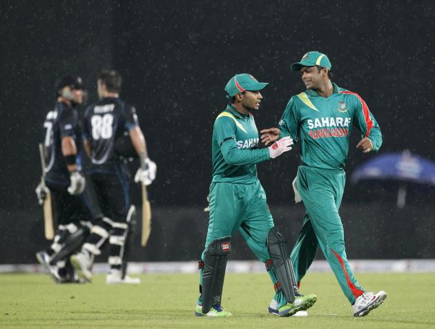 Bangladesh's captain Rahim and Razzak leave the field after rain inturupted the first one-day international (ODI) cricket match between New Zealand and Bangladesh in Dhaka.