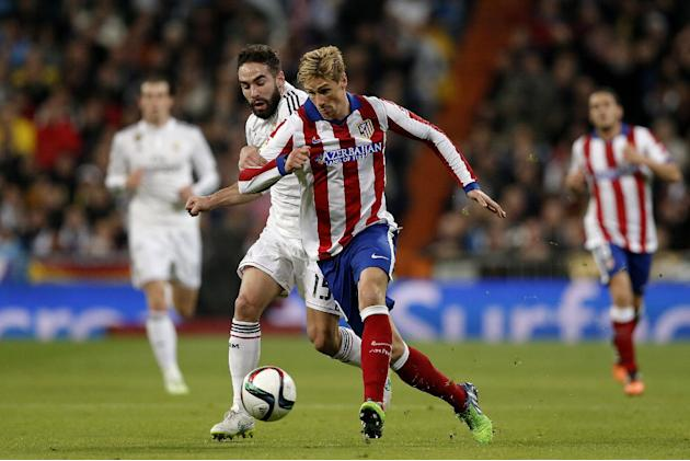 Real Madrid's Daniel Carvajal, left, duels for the ball with Atletico de Madrid's Fernando Torres during a King's Cup soccer match between Atletico de Madrid and Real Madrid, at the Santiago Bernabeu