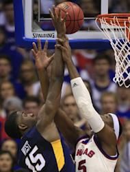 West Virginia forward Lamont West, left, is fouled by Kansas forward Carlton Bragg Jr., during the first half of an NCAA college basketball game in Lawrence, Kan., Monday, Feb. 13, 2017. (AP Photo/Orlin Wagner)