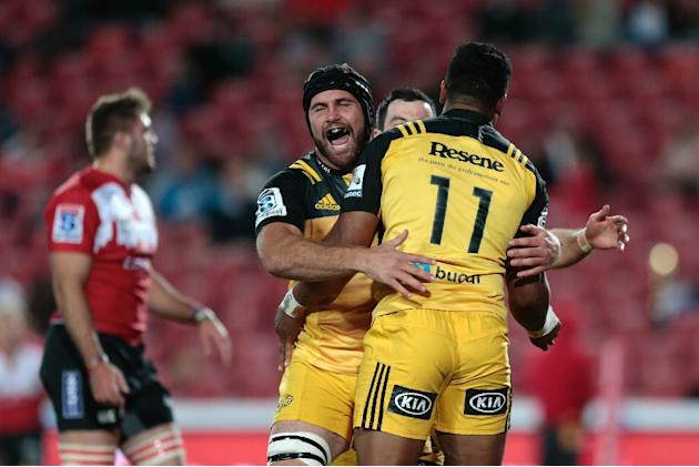 Wellington Hurricanes' flanker Callum Gibbins (L) congratulates wing Julian Savea (R) after he scored a try during the Super Rugby clash between Lions and Hurricanes on April 30, 2016 in Johannesb