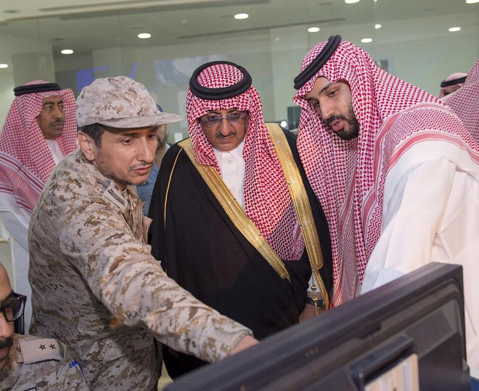 Saudi Defence Minister Prince Mohammad bin Salman and Saudi interior Minister and Deputy Crown Prince Mohammed bin Nayef are briefed by officers on the military operations in Yemen at the command cent