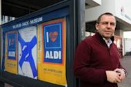 "Reinhard Spieler, director of the Wilhelm Hack museum in Ludwigshafen, western Germany, poses in front of an advertisement of German discounter Aldi displayed at the exibition ""I love Aldi"" at the Wilhelm Hack Museum in Ludwigshafen am Rhein, western Germany"