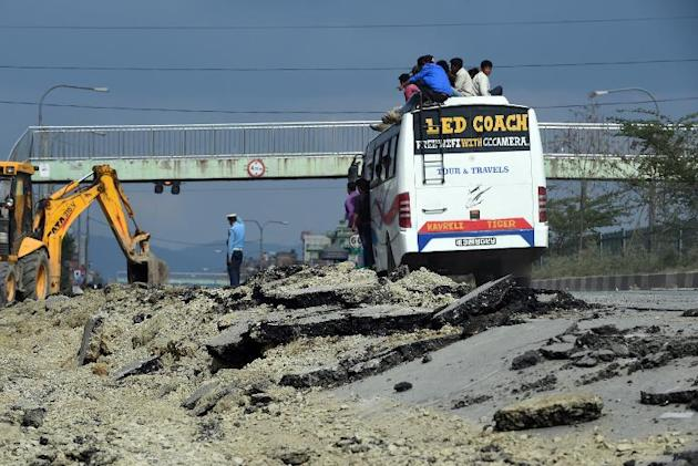Nepalese people travel on the roof of a bus as they drive past a damaged road on the outskirts of Kathmandu on April 26, 2015