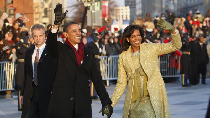 FILE - In this Jan. 20, 2009, file photo, President Barack Obama and first lady Michelle Obama walk the inaugural parade route in Washington. Obama's second inauguration is shaping up as a high-energy celebration smaller than his first milestone swearing-in, yet still designed to mark his unprecedented role in American history with plenty of eye-catching glamour. A long list of celebrity performers will give the once-every-four years right of democratic passage the air of a star-studded concert, from the bunting-draped Capitol's west front of the Capitol, where Obama takes the oath Jan. 21, to the Washington Convention Center, which is expected to be packed with 40,000 ball-goers that evening. (AP Photo/Charles Dharapak)