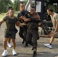 In this photo, released by the Philippine Army's Western Mindanao Command, a wounded Philippine soldier is carried by his comrades after a clash with the country's largest Muslim guerrilla group,the Moro Islamic Liberation Front (MILF), in Basilan, southern Philippines, on October 18