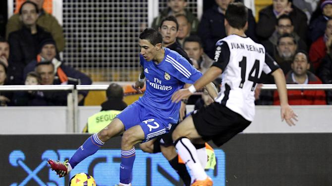 Real Madrid's  Angel Di Maria from Argentina duels for the ball with Valencia's Juan Bernat   during their La Liga soccer match at the Mestalla stadium in Valencia, Spain, Sunday, Dec. 22, 2013