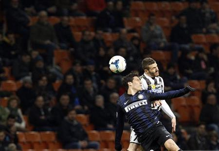 Inter Milan's Hernanes (L) jumps for the ball with Udinese's Thomas Heurtaux during their Italian Serie A soccer match at San Siro stadium in Milan March 27, 2014. REUTERS/Alessandro Garofalo