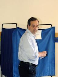 A handout photo provided by the New Democracy party press office shows the leader of the conservative New Democracy party, Antonis Samaras, preparing to cast his ballot at a polling station in his hometown of Pylos in the southern Peloponnese peninsula. Greece's two main pro-bailout parties clinched enough votes to form a government in a cliffhanger election on Sunday, early results showed