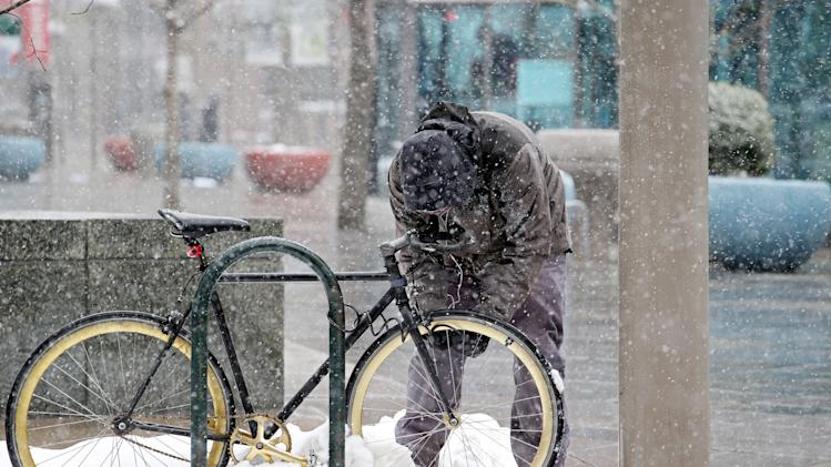 A messenger locks up his bike during a storm  in Denver on Wednesday, April 17, 2013. As much as five inches of new snow is forecast for Denver. (AP Photo/Ed Andrieski)