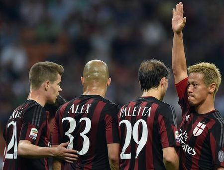 AC Milan's Honda gestures with his team mates during their Serie A soccer match against AS Roma at the San Siro stadium in Milan