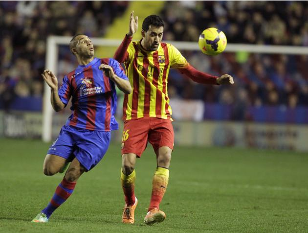 Barcelona's Busquets and Levante's El Zhar fight for the ball during their Spanish First Division soccer match at the Ciudad de Valencia stadium in Valencia