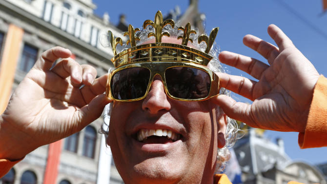 A man wearing a crown, adjusts his sunglasses as he poses for photographers in downtown Amsterdam, Netherlands Monday, April 29, 2013. Queen Beatrix has announced she will relinquish the crown on April 30, 2013, after 33 years of reign, leaving the monarchy to her son Crown Prince Willem-Alexander. (AP Photo/Vincent Jannink)
