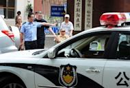 A policeman pictured standing next to his car in Beijing on May 9. Police arrested an ex-Communist Party official in central China on suspicion of raping at least 10 underage girls, authorities said Sunday, in a case that has sparked a storm of Internet anger