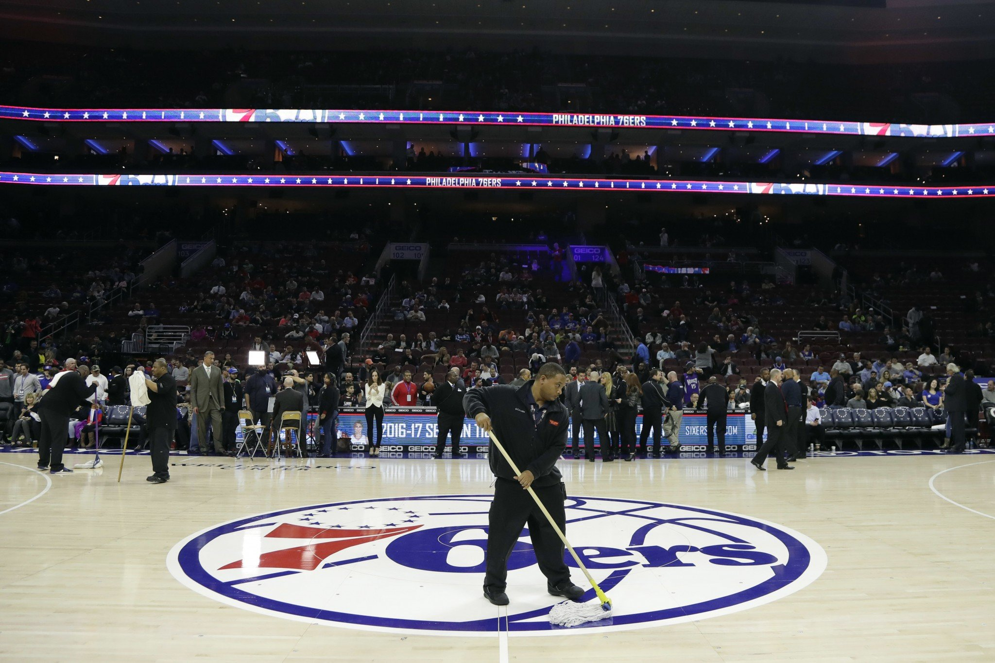 A building worker wipes the court before an NBA basketball game between the Philadelphia 76ers and the Sacramento Kings, Wednesday, Nov. 30, 2016, in Philadelphia. The start of the game was delayed due to a surface issue with the court. (AP)