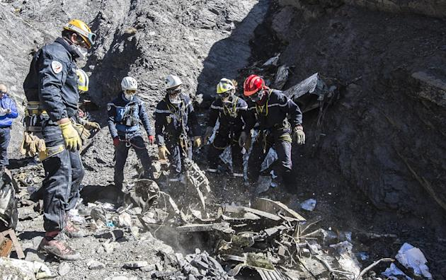 In this photo taken on Tuesday, March 31, 2015 and provided by the French Interior Ministry, French emergency rescue services work among debris of the Germanwings passenger jet at the crash site near