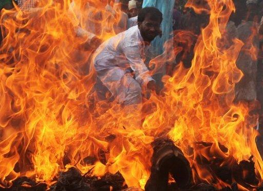 An Indian Muslim student hits a burning effigy of US President Barack Obama as others shout anti-US slogans during a protest against an anti-Islam movie in Kolkata. As protests again erupted across the Muslim world on Wednesday over an anti-Islam film, a French magazine poured fuel on the fire by publishing obscene cartoons depicting the Prophet Mohammed
