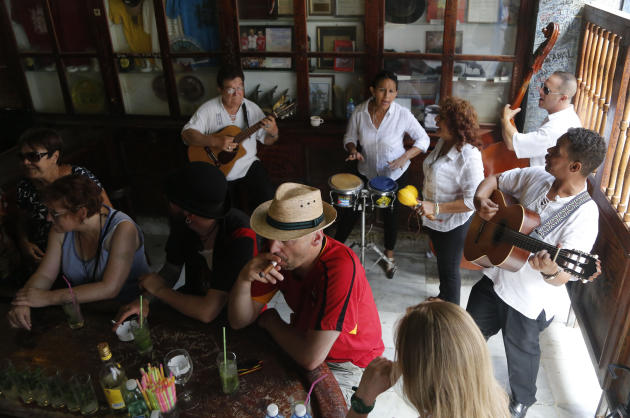 In this Sunday, May 24, 2015 photo, tourists enjoy cigars, mojitos and live music at the Bodeguita del Medio Bar, frequented by the late American novelist Ernest Hemingway in Old Havana, Cuba. The tha