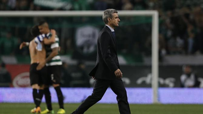 FC Porto's coach Luis Castro leaves the pitch as Sporting players hug in the background at the end of their Portuguese league soccer match Sunday, March 16 2014, at Sporting's Alvalade stadium in Lisbon. Sporting won 1-0