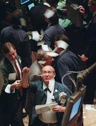 File - In this Nov. 21, 1995 file photo, a New York Stock Exchange trader throws tickets into the air on the floor of the exchange as it closes, in New York. The Dow Jones industrial average closed in record territory over the milestone 5,000 mark for the first time in history. When it comes to Wall Street, big, round numbers make people take notice. Dow 13,000, reached earlier this week for a few brief minutes, was the latest example. (AP Photo/Adam Nadel, File)