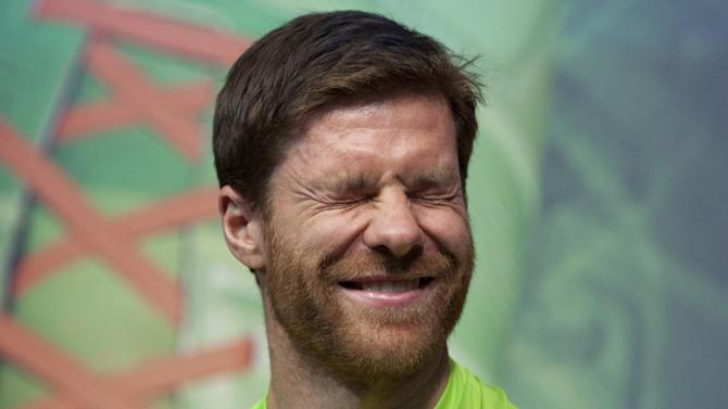 Real Madrid's Xabi Alonso shuts his eyes while taking part in a soccer boot promotional event in Madrid, Spain. Thursday Nov. 21, 2013