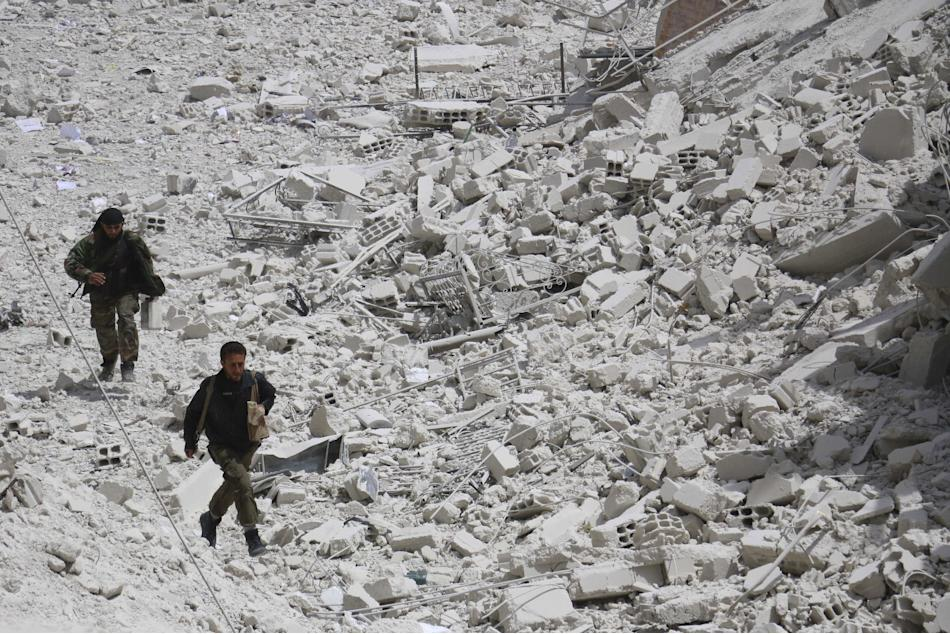 Free Syrian Army fighters run for cover amid rubble of collapsed buildings from shelling by forces loyal to Syria's President Bashar Al-Assad on Zabdin village, a suburb of Damascus
