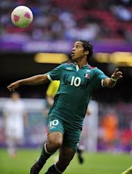 Mexico's striker Giovani Dos Santos eyes the ball during the London 2012 Olympic Games men's football match between Mexico and Switzerland at the Millennium Stadium in Cardiff, Wales, on August 1, 2012. AFP PHOTO / GLYN KIRK