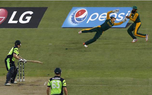 Ireland's O'Brien watches as South Africa's wicketkeeper Quinton de Kock dives and Amla takes a catch under his arm to dismiss him for 14 runs during their Cricket World Cup match at Manuk