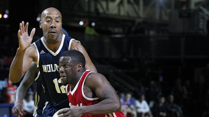 East's Bruce Bowen (12) reaches for West's Kevin Hart, foreground, in the second half as they participate in the NBA All-Star Celebrity basketball game in New Orleans, Friday, Feb. 14, 2014. East won 60-56