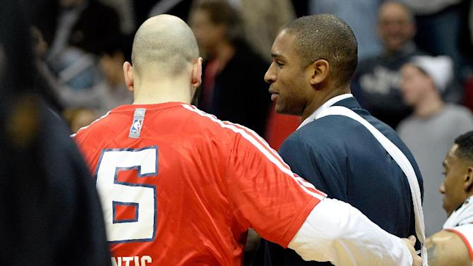Atlanta Hawks center Al Horford, right, is consoled by teammate Pero Antic as he joins the team for a timeout in the overtime period of their NBA basketball game against the Charlotte Bobcats on Saturday, Dec. 28, 2013, in Atlanta. Horford tore his right pectoral muscle earlier this week against the Cleveland Cavaliers and is out indefinitely, according to the team