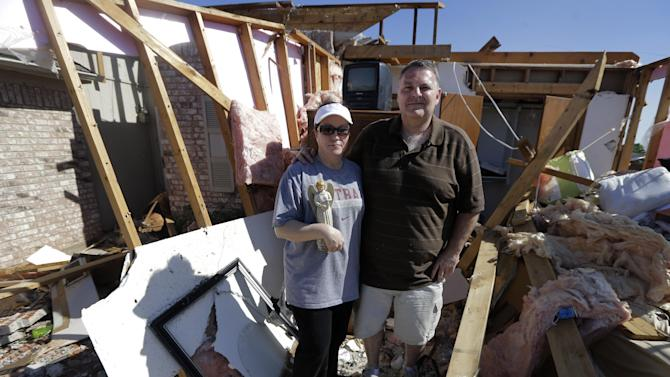 In this Wednesday, May 22, 2013 photo, Cindy Sasnett clings to a porcelain Christmas angel decoration she recovered from her destroyed home as she and her husband Jim stand in one of their destroyed bedrooms where she almost took refuge from Monday's tornado, in Moore, Okla. They say you should never make a big decision when you're emotional. But what if there's barely a moment to think and a life-or-death choice looming? (AP Photo/Tony Gutierrez)