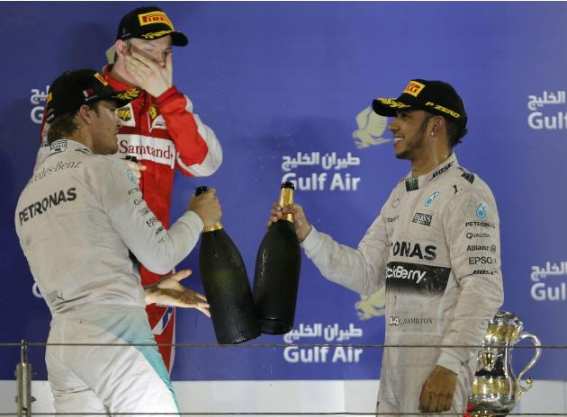Mercedes driver Hamilton of Britain celebrates his victory on the podium on the podium with team mate Rosberg of Germany after Bahrain's F1 Grand Prix