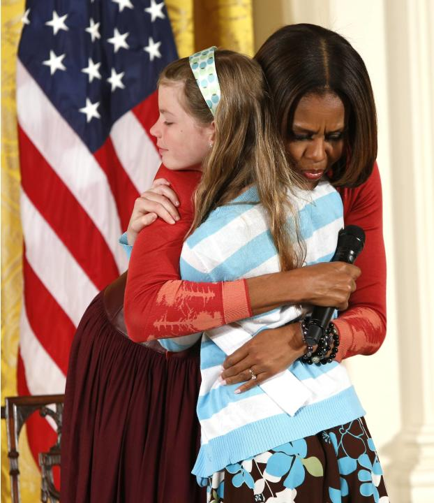 First Lady Michelle Obama hugs Bell, who gave the first lady her father's resume and said he had been out of work for three years, in Washington