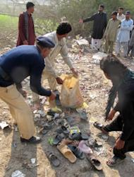 A policeman and Muslims collect the slippers of blast victims at the site of a bomb explosion in Dera Ismail Khan in Khyber Pakhtunkhwa province on Saturday