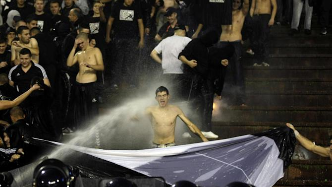 A Partizan Belgrade supporter is hit by a water cannon during his team's Serbian league soccer game against arch rivals Red Star in Belgrade, Serbia, Saturday, Nov. 2, 2013. Violence on the stands during soccer matches is becoming a regular occurrence in Serbian league soccer