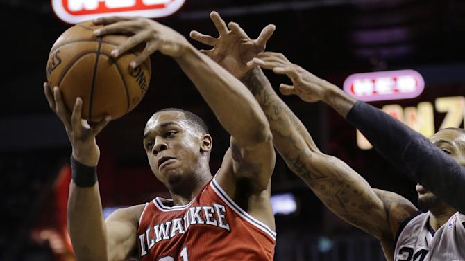 Milwaukee Bucks' John Henson (31) grabs a rebound in front of San Antonio Spurs' Malcolm Brown (24) during the second half of an NBA basketball game, Sunday, Jan. 19, 2014, in San Antonio. San Antonio won 110-82