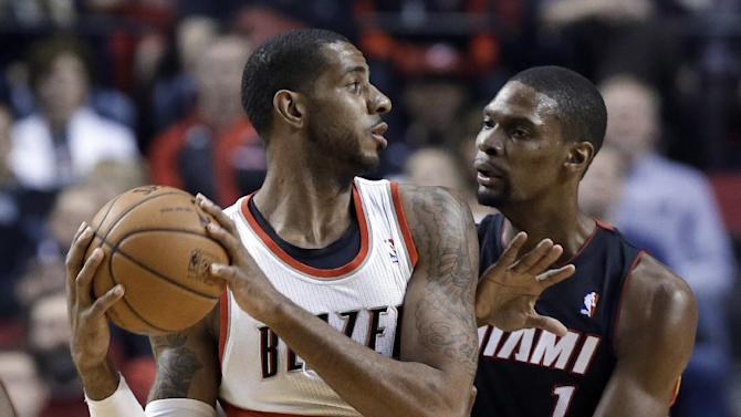 Portland Trail Blazers forward LaMarcus Aldridge, left, looks to pass as Miami Heat center Chris Bosh defends during the first half of an NBA basketball game in Portland, Ore., Saturday, Dec. 28, 2013