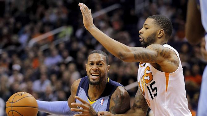 Memphis Grizzlies' James Johnson, left, drives past Phoenix Suns' Markieff Morris (15) during the first half of an NBA basketball game on Thursday, Jan. 2, 2014, in Phoenix