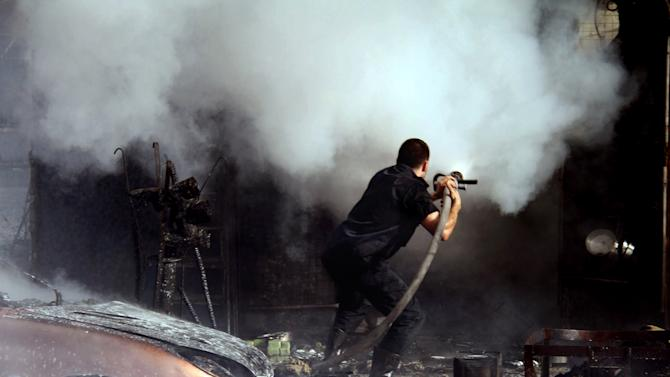 In this photo released by the Syrian official news agency SANA, a Syrian firefighter extinguishes at the scene where two mortar rounds exploded near an orphanage, at al-Boukhtyar area, in Damascus, Syria, Wednesday March 13, 2013. The state-run SANA news agency said two mortar rounds exploded near an orphanage in al-Boukhtyar area, killing and wounding an unknown number of people. Syrian government troops fought fierce battles with rebels on Wednesday for control of key neighborhoods in the north of Damascus, residents and activists said. (AP Photo/SANA)